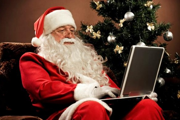Traditional Santa Claus with a modern laptop
